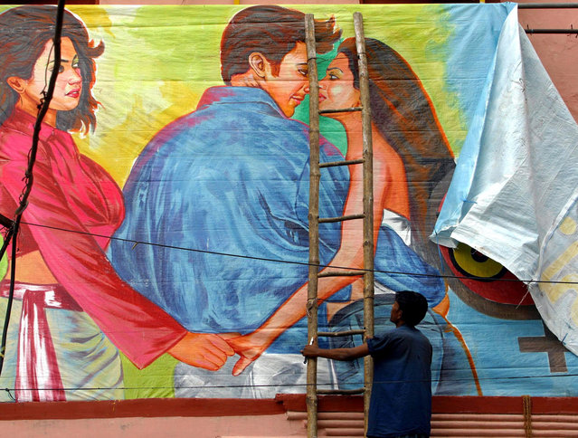 """In this June 15, 2004 file photo, a movie theatre worker removes a poster of Bollywood film """"Girlfriend"""" in Allahabad, India, after Hindu hard-liners smashed glass panes and ripped posters in cinemas to pressure the government to censor or ban the film about a lesbian couple. Between 2014-2015, India has banned at least two books, as many films, one state has banned eating beef, and the film censor board issued a list of words they consider unacceptable for the delicate ears of adult Indians. (Photo by Rajesh Kumar Singh/AP Photo)"""