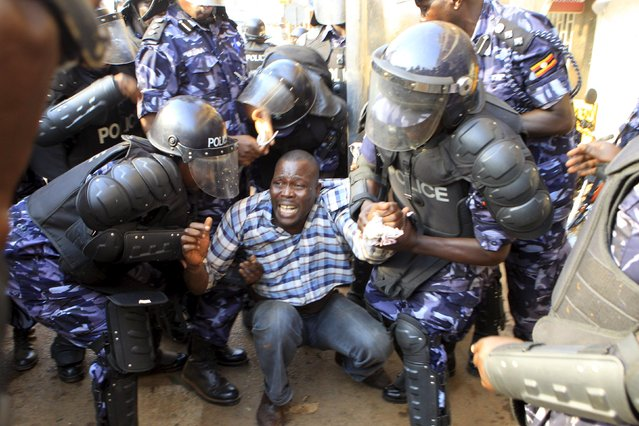 Riot police detain a supporter of Uganda's leading opposition party Forum for Democratic Change as police and military forces disperse their procession with their presidential candidate to a campaign ground in Kampala, Uganda, February 15, 2016. (Photo by James Akena/Reuters)