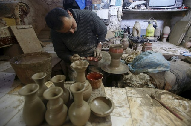 Palestinian Jamal Fakhori paints clay jars and pots in his pottery workshop in the West Bank village of Jabaa near Jenin January 31, 2016. (Photo by Abed Omar Qusini/Reuters)