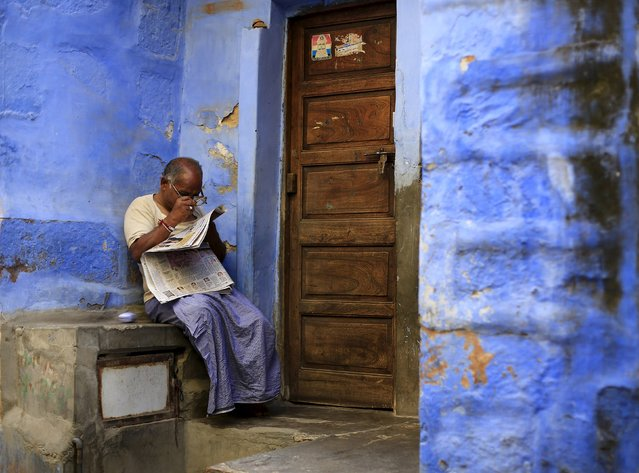 A local resident reads a newspaper outside his house at Jodhpur in Rajasthan, April 7, 2015. (Photo by Adnan Abidi/Reuters)