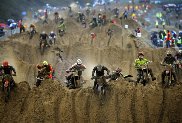 Riders reach the crest of a dune during the opening lap of the main race of the 2013 RHL Weston beach race in Weston-Super-Mare, southwest England, on October 13, 2013. (Photo by Adrian Dennis/AFP Photo)