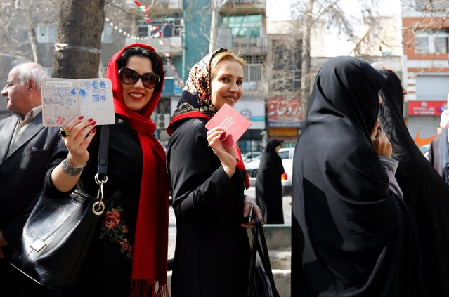Iranian women show their IDs as they wait in line to cast their votes in the parliamentary and Experts Assembly election outside a polling station at Ershad Mosque in Tehran, Iran, 26 February 2016. Voting began in Iran's parliamentary elections, which mark the first test of the political mood since Iran's nuclear deal with major powers reached in July. More than 4,800 candidates are running for 290 seats. (Photo by Abedin Taherkenareh/EPA)