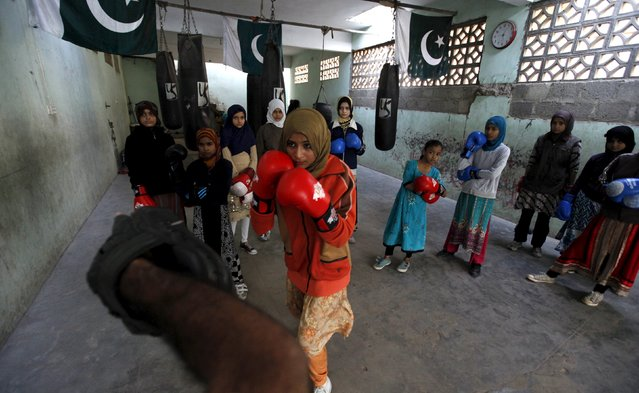 Anum, 17, punches padding with her coach Younus Qambrani while others observe during an exercise session at the first women's boxing coaching camp in Karachi, Pakistan February 20, 2016. (Photo by Akhtar Soomro/Reuters)