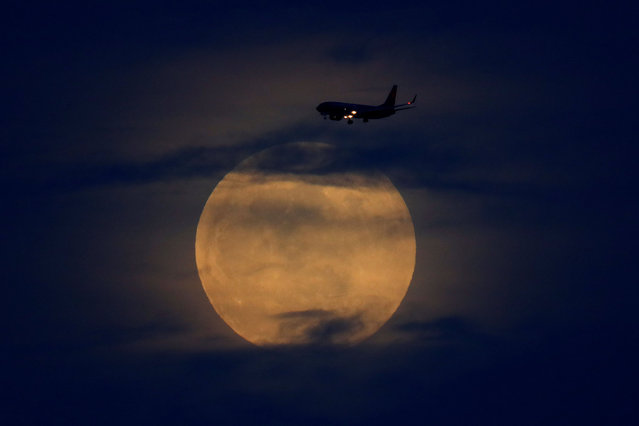 """A full moon rises between clouds as a landing commercial jet approaches the airport before the start of a total lunar eclipse that is being called a """"Super Blood Wolf Moon"""" in San Diego, California, U.S., January 20, 2019. (Photo by Mike Blake/Reuters)"""