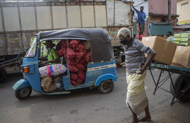 A Sri Lankan man transports a load of imported onions and garlic in an autorickshaw as an elderly laborer pulls a load of goods at a wholesale market during travel restrictions imposed to curb the spread of coronavirus in Colombo, Sri Lanka on June 16, 2021. (Photo by Eranga Jayawardena/AP Photo)