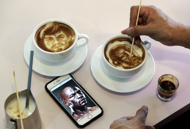 Filipino graphic artist and barista Zach Yonzon, draws the faces of Filipino boxer Manny Pacquiao and American boxer Floyd Mayweather Junior on two coffee latte inside a Cafe and Cake Studio in Manila, Philippines, 23 April 2015. Yonzon draws different faces on the top of a coffee latte upon costumers' requests. (Photo by Ritchie B. Tongo/EPA)