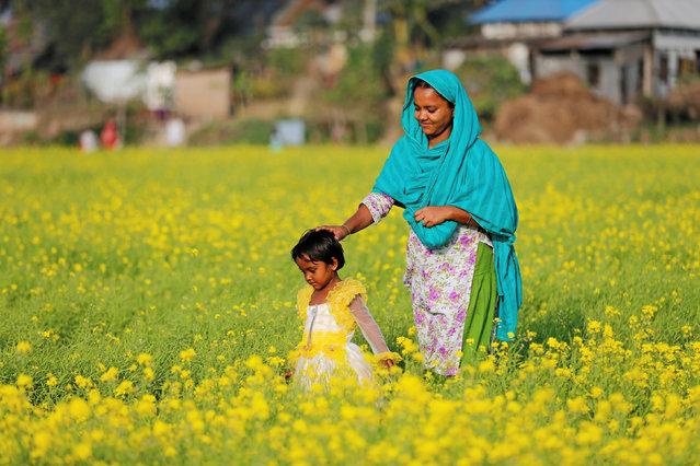 A Bangladeshi woman and her child walks on a mustard field in Munshiganj near Dhaka, Bangladesh, January 20, 2017. (Photo by Mohammad Ponir Hossain/Reuters)