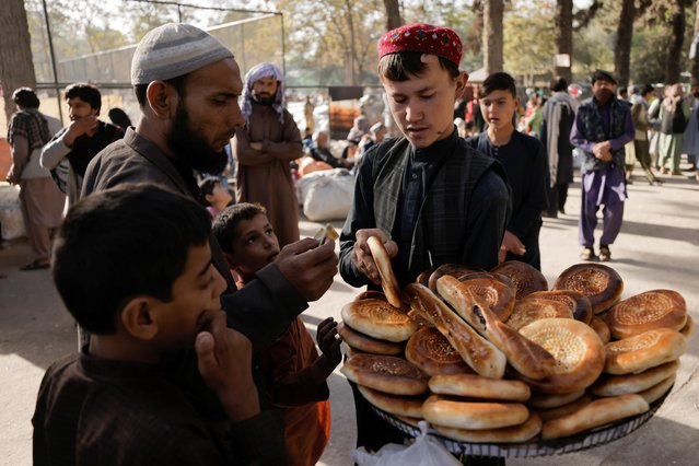 A boy sells bread at a makeshift shelter for displaced Afghan families, who are fleeing the violence in their provinces, at Shahr-e Naw park, in Kabul, Afghanistan October 4, 2021. (Photo by Jorge Silva/Reuters)