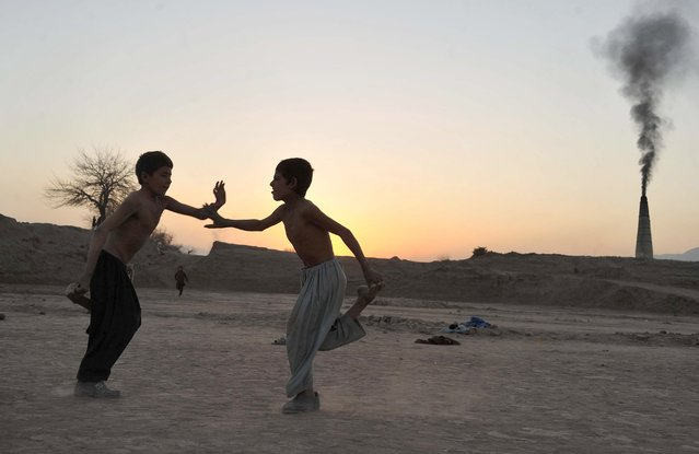 Afghan children play Ghursai, a traditional boy's game, in the countryside on the outskirts of Jalalabad, Nangarhar province on January 28, 2014. Children hold one foot in one hand and then try to knock down their opponent. (Photo by Noorullah Shirzada/AFP Photo)