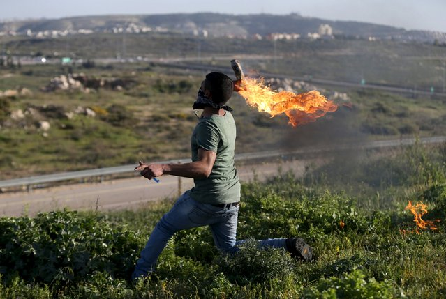 A Palestinian protester hurls a molotov cocktail towards Israeli troops during clashes, near Israel's Ofer Prison near the West Bank city of Ramallah, March 11, 2016. (Photo by Mohamad Torokman/Reuters)
