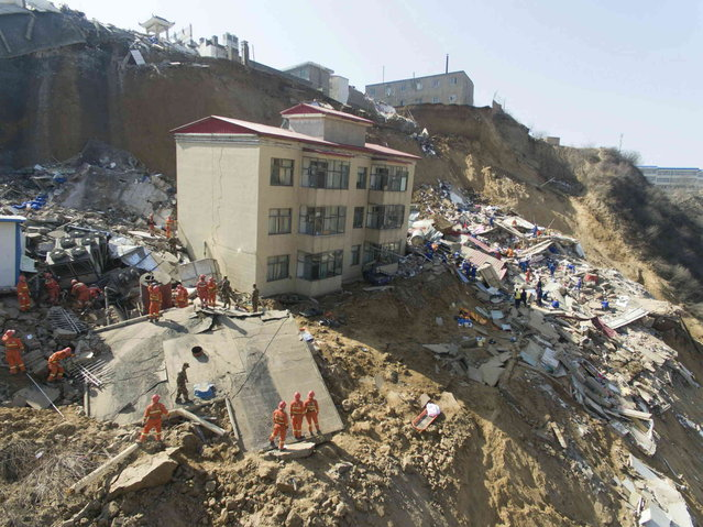 Rescue workers search the site of a landslide that caused buildings to collapse in Xiangning county in northern China's Shanxi province Saturday, March 16, 2019. Hundreds of police, firefighters and medical personnel joined rescue efforts on Saturday after a landslide in northern China knocked down several buildings, killing some and leaving others missing. (Photo by Chinatopix via AP Photo)
