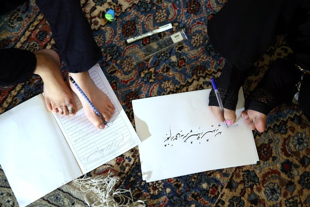 In this picture taken on Wednesday, January 21, 2015, Zohreh Etezadossaltaneh, right, teaches calligraphy to 9-year old Afghan boy Roohollah Jafar, at her home, in Tehran, Iran. The boy lost his hands in an accident and is now learning from Etezadossaltaneh to paint and do calligraphy using his feet. At the start of their lesson, Etezadossaltaneh skillfully massages the boy's feet with her own feet and guides him on how to hold and control a pen. (Photo by Ebrahim Noroozi/AP Photo)