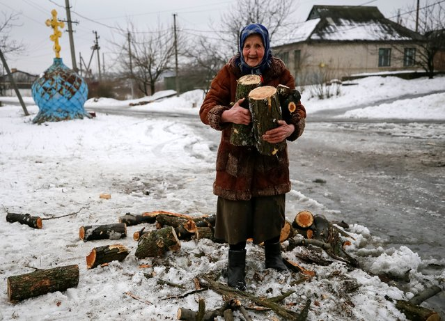 An elderly woman carries firewood for heating her home in the government-held industrial town of Avdiyivka, Ukraine February 5, 2017. (Photo by Gleb Garanich/Reuters)