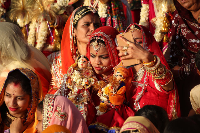 In this photo taken on April 8, 2019, Indian married women take a selfie on a smartphone as they take part in the Gangaur festival in Udaipur, in India's western Rajasthan state, to worship the Hindu goddess Gauri, consort of the deity Shiva. (Photo by Himanshu Sharma/AFP Photo)