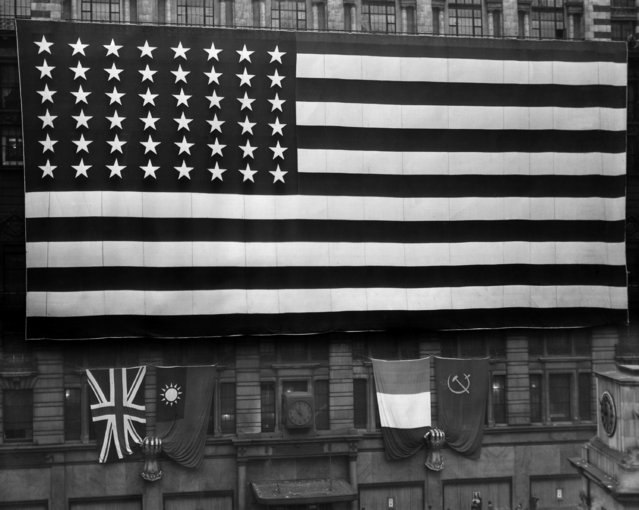 A huge American flag unfurled in New York's Herald Square on VE Day on May 8, 1945. This 80x160 foot flag was hung from the eighth floor balcony of Macy's New York department store, covering the façade from 34th and 35th Streets along Broadway. Beneath it were placed a set of British, Chinese, French and Russian flags, held by two giant mailer fists. (Photo by AP Photo)