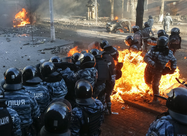 Riot policemen stand guard as they are hit by fire caused by molotov cocktails hurled by anti-government protesters during clashes in Kiev February 18, 2014. Ukrainian riot police charged protesters occupying a central Kiev square early on Wednesday after the bloodiest day since the former Soviet republic, caught in a geopolitical struggle between Russia and the West, won its independence more than 22 years ago. (Photo by Reuters/Stringer)