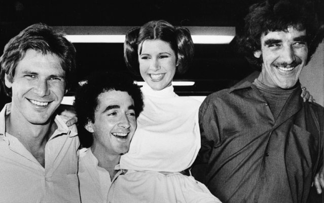 """In this October 5, 1978 file photo, actors featured in the """"Star Wars"""" movie, from left, Harrison Ford who played Han Solo, Anthony Daniels who played the robot C3P0, Carrie Fisher who played the princess, and Peter Mayhew who played the Wookie, Chewbacca, are shown during a break from the filming of a television special presentation in Los Angeles. Mayhew, who played the rugged, beloved and furry Wookiee Chewbacca in the """"Star Wars"""" films, has died. Mayhew died at his home in north Texas on Tuesday, April 30, 2019 according to a family statement. He was 74. No cause was given. (Photo by AP Photo/File)"""