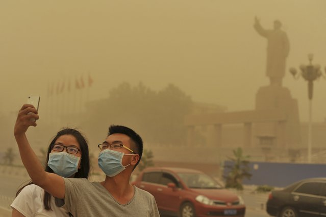 A couple wears facemarks as they pose for a self-portrait near a large statue of late Chinese leader Mao Zedong during a sandstorm in Kashgar city in northwestern China's Xinjiang Uighur Autonomous Region, Sunday May 10, 2015. (Photo by Chinatopix via AP Photo)