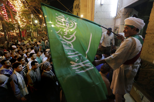 """In this photo taken Tuesday, May 12, 2015, an Egyptian Sufi Muslim waves a green flag with Arabic that reads, """"There is no God but Allah and Muhammad is his messenger"""" as he welcomes visitors to the Sayyeda Zeinab mosque. Egyptian Muslims celebrate the religious festival, or Moulid, which commemorates the birth of the Muslim Prophet Muhammad's granddaughter, Sayyeda Zeinab, outside the mosque and shrine named for her, in Cairo, Egypt. (Photo by Amr Nabil/AP Photo)"""