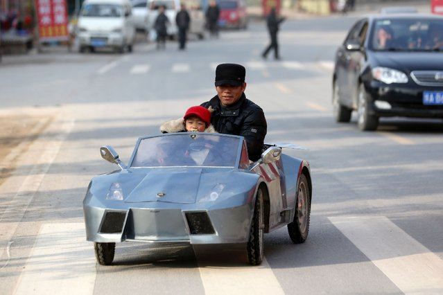 "This picture taken on February 19, 2014 shows Guo (R), a farmer in his 50s, sits in his self-made scale replica of a Lamborghini with his grandson in a street in Zhengzhou, central China's Henan province. Guo spent 6 months and about 5,000 yuan ($821) to make the 2-meter-long, 1 meter wide ""lamborghini"" as a toy for his grandson. (Photo by AFP Photo)"