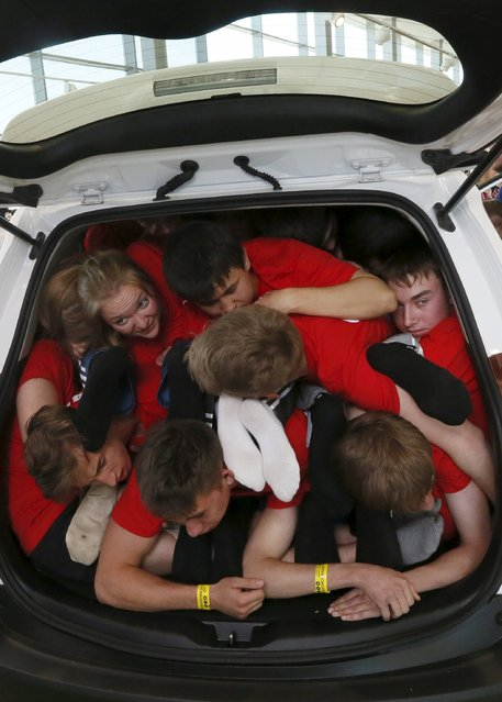 Students from the Siberian State Technological University team squeeze into a car during a local competition and attempt for a Guinness Book of World Records for the most number of people in a car in Krasnoyarsk, Russia, May 16. 2015. (Photo by Ilya Naymushin/Reuters)
