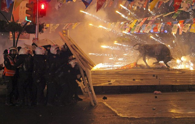 Riot policemen shield themselves as fireworks thrown by protesters explode next to the statue of a bull, during an anti-government protest in the Kadikoy district of Istanbul March 11, 2014. Protesters clashed with police in cities across Turkey on Tuesday after the death of a 15-year-old boy who was hit in the head by a tear-gas canister during anti-government demonstrations last summer. (Photo by Reuters/Stringer)