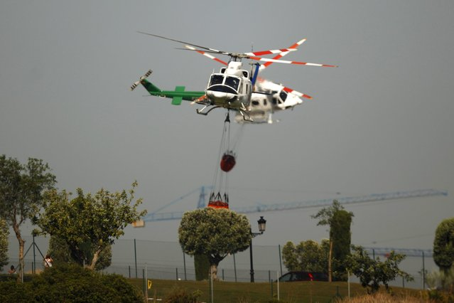 Helicopters carrying water fly to drop water over a wildfire in Benahavis, southern Spain, May 19, 2015. (Photo by Jon Nazca/Reuters)