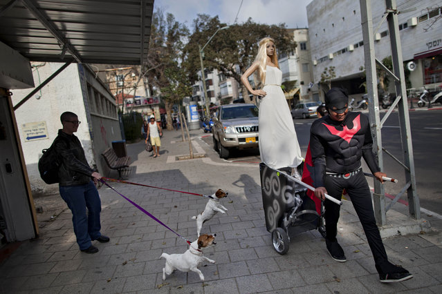 A costume shop employee, dressed as batman, pulls a cart with a mannequin to advertise the shop, ahead of the upcoming Jewish holiday of Purim, in Tel Aviv, Israel, Sunday, February 10, 2013. (Photo by Oded Balilty/AP Photo)