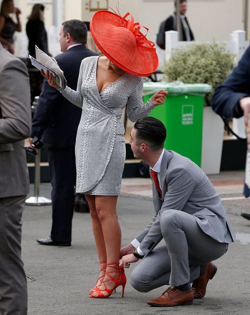 Chivalry is alive and well: racegoers attends Ladies Day of the Crabbie's Grand National Festival at Aintree Racecourse on April 8, 2015 in Liverpool, England. (Photo by Peter Byrne/PA Wire)