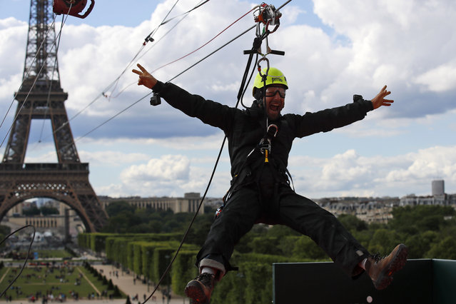A participant rides a zipline tied from the second floor of the Eiffel Tower, 115 metres above the Champ de Mars gardens along an 800-meters long cable, as part of a free event in Paris, France, Tuesday, May 28, 2019. (Photo by Francois Mori/AP Photo)