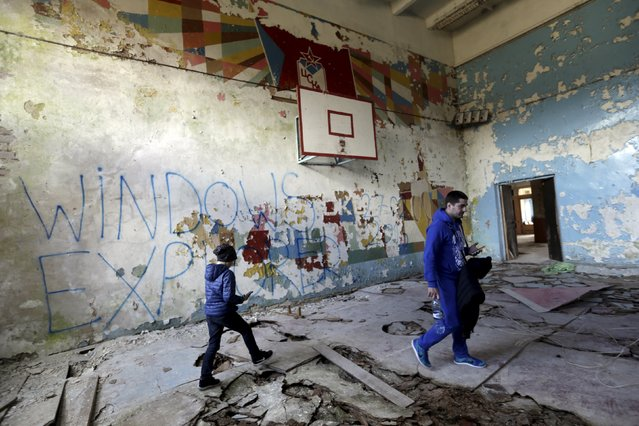 People walk inside abandoned sports hall in the ghost town of a former Soviet military radar station near Skrunda, Latvia, April 9, 2016. (Photo by Ints Kalnins/Reuters)