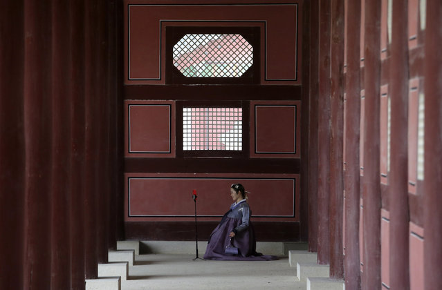 """In this Wednesday, March 27, 2019, file photo, a woman dressed in South Korean traditional """"Hanbok"""" attire poses to take pictures at the Gyeongbok Palace, the main royal palace in the Joseon Dynasty, in Seoul, South Korea. Wearing a """"Hanbok"""", mostly rented, has become a fashionable trend among the youth commonly seen at palaces and other traditional places. (Photo by Ahn Young-joon/AP Photo)"""