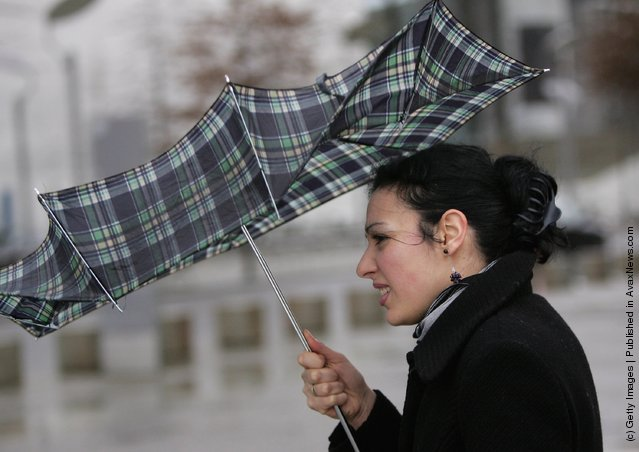 A woman holds on to her umbrella despite strong winds