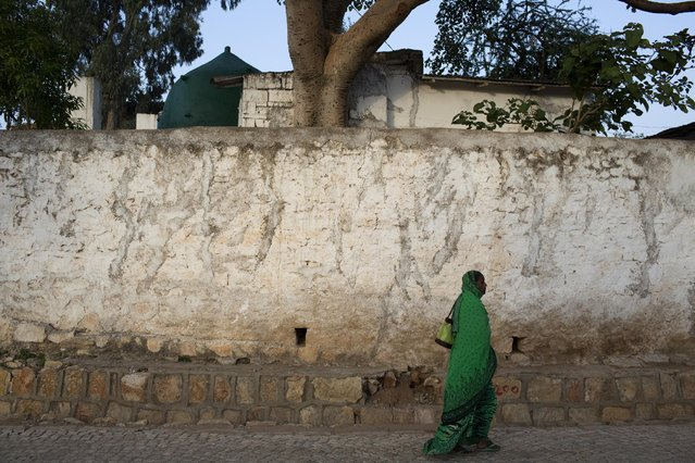 A woman walks past the outside wall of the old town of Harar in eastern Ethiopia, May 20, 2015. Daily life of people in Ethiopia, where elections are held this weekend, is portrayed in the east African nation's churches and mosques, coffee shops and markets, both in the capital Addis Ababa and the walled town of Harar in the east. (Photo by Siegfried Modola/Reuters)