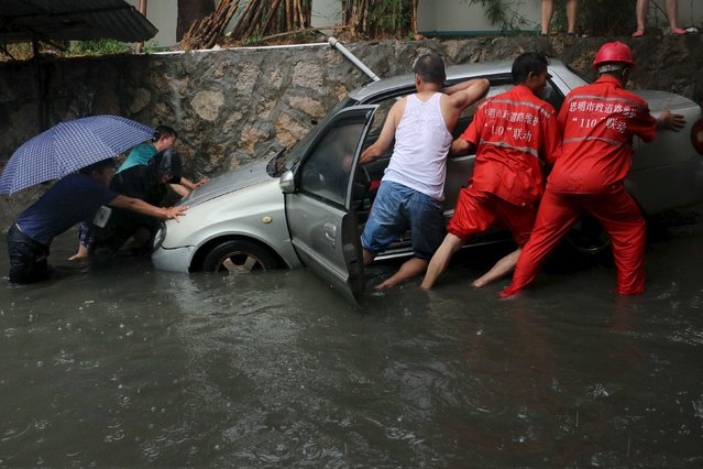 People try to move a car stuck on a flooded street in heavy rainfall in Xiamen, Fujian province, China, May 20, 2015. (Photo by Reuters/Stringer)