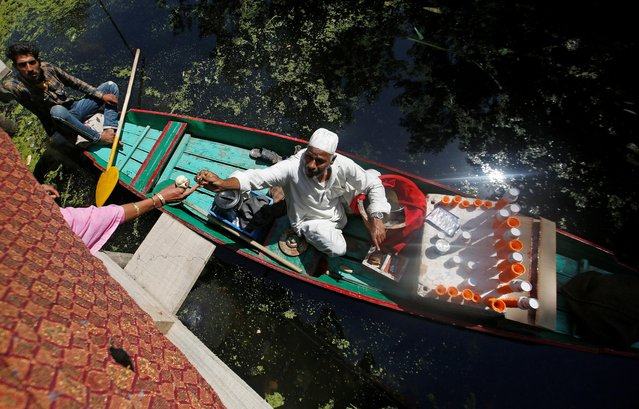 A vendor sitting on a boat sells ice cream at Dal Lake in Srinagar, June 27, 2019. (Photo by Danish Ismail/Reuters)