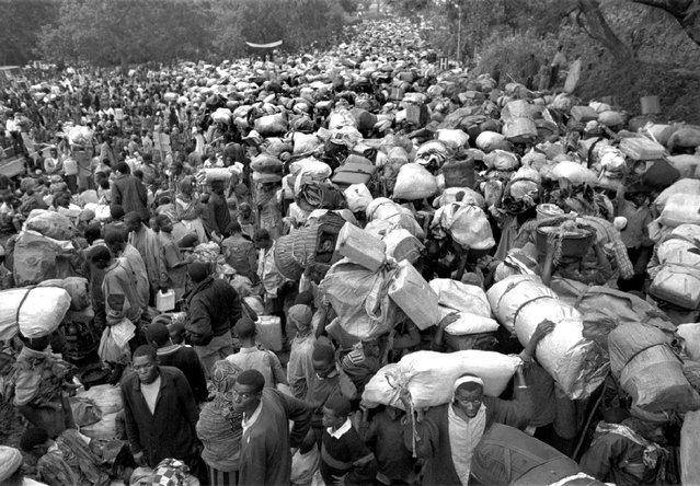Hundreds of thousands of refugees stream along the main road in Gisenyi, Rwanda, after crossing the border from Mugunga refugee camp in Zaire; 1996. (Photo by Carol Guzy/The Washington Post)