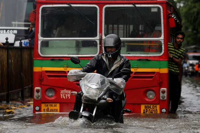 A man rides a motorcycle through a water-logged street during heavy rains in Mumbai, July 1, 2019. (Photo by Francis Mascarenhas/Reuters)