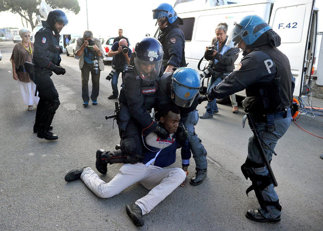 Italian police officers remove a migrant in Ventimiglia, at the Italian-French border Tuesday, June 16, 2015. Police at Italy's Mediterranean border with France forcibly removed a few dozen African migrants who have been camping out for days in hopes of continuing their journeys farther north, a violent scene Italy is using to show that Europe needs to do something about the migrant crisis. (Luca Zennaro/ANSA via AP)