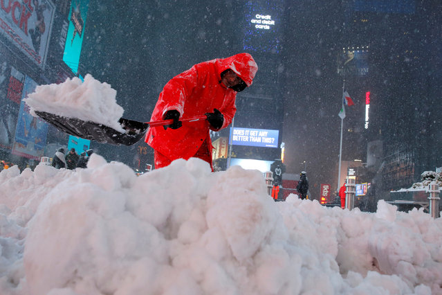 A worker clears snow in Times Square as snow falls in Manhattan, New York, U.S., March 14, 2017. (Photo by Andrew Kelly/Reuters)