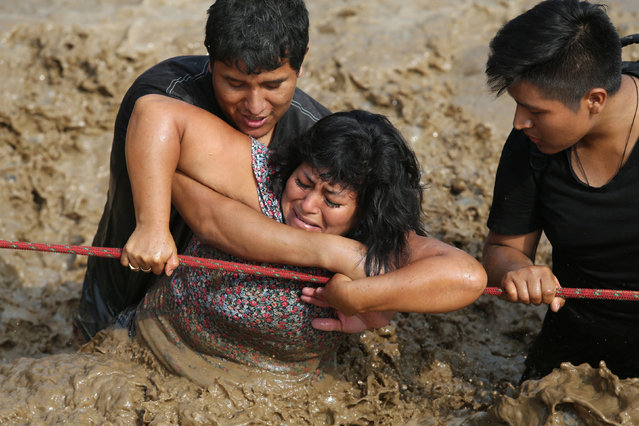A woman is assisted while crossing a flooded street after the Huayco river overflooded its banks sending torrents of mud and water rushing through the streets, in Huachipa, Peru on March 17, 2017. (Photo by Guadalupe Pardo/Reuters)