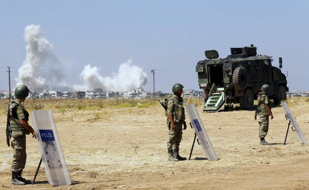 Turkish soldiers stand guard near the Mursitpinar border gate in Suruc in Sanliurfa province as smoke rises in the Syrian town of Kobani in the background June 27, 2015. An explosion hit the Syrian town of Kobani on Saturday, a witness said, sending plumes of smoke into the air days after the town suffered an attack by Islamic State militants that killed at least 145 people. (Photo by Murad Sezer/Reuters)