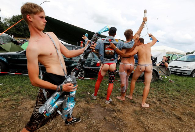 A festival goer from the Bavarian town of Diessen near Munich plays air guitar made of empty beer cans as his scantily dressed friends perform a heavy metal song at the world's largest heavy metal festival, the Wacken Open Air 2019, in Wacken, Germany on August 3, 2019. (Photo by Wolfgang Rattay/Reuters)