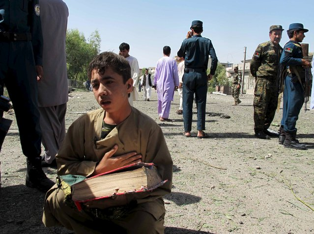 An Afghan boy holds a copy of the Koran at the site of an attack on police headquarters in the provincial capital, Lashkar Gah of the southern Helmand province, Afghanistan, June 30, 2015. At least two civilians died and more than forty were injured during suicide car bomb attack in Lashkar Gah, police said. (Photo by Abdul Malik/Reuters)