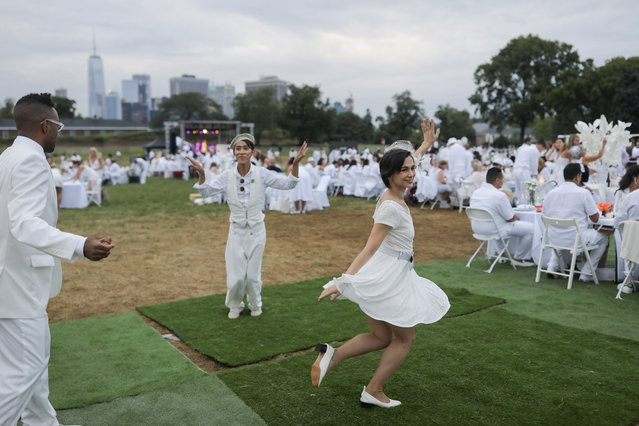 Diner En Blanc, a secret pop up dinner, is held this year on Governors Island in New York, U.S., September 17, 2018. (Photo by Stephen Yang/Reuters)
