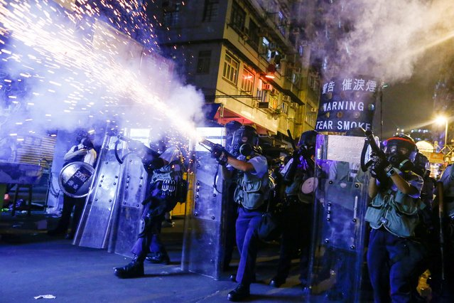 Police fire tear gas at anti-extradition bill protesters during clashes in Sham Shui Po, Hong Kong, China, August 14, 2019. Hundreds attended a demonstration in the residential area of Sham Shui Po, where police arrived and quickly used tear gas after protesters pointed lasers at the police station and burned joss papers on the roadside. (Photo by Thomas Peter/Reuters)