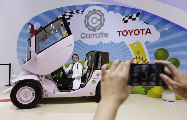A visitor poses for a photo in a Toyota Camatte car at Auto China 2014 in Beijing, April 20, 2014. Toyota aims to double auto sales in China to around 2 million vehicles a year in the future, a senior executive said on Sunday, as the top global car maker plays catch up to rivals, such as Volkswagen, in the world's largest auto market. (Photo by Jason Lee/Reuters)