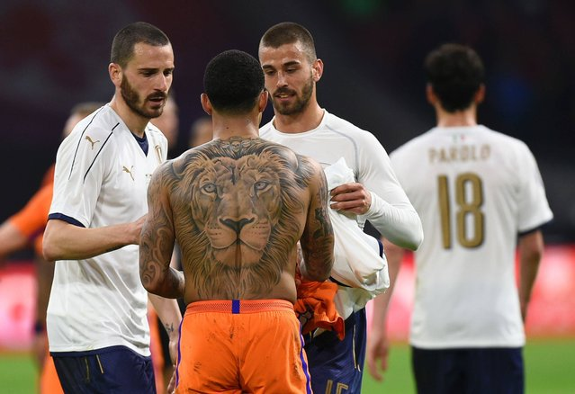 Netherland's Memphis Depay (C) exchanges his shirt with Italy's Leonardo Spinazzola (R) during the friendly football match between The Netherlands and Italy at the Arena Stadium, on March 28, 2017 in Amsterdam. (Photo by John Thys/AFP Photo)