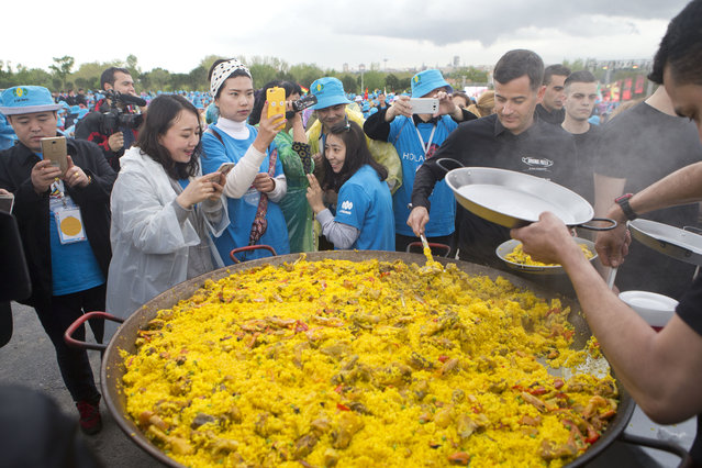 Chinese conglomerate Tiens Group employers take photos while waiting to be served Paella in Madrid, Spain, Friday, May 6, 2016. (Photo by Paul White/AP Photo)