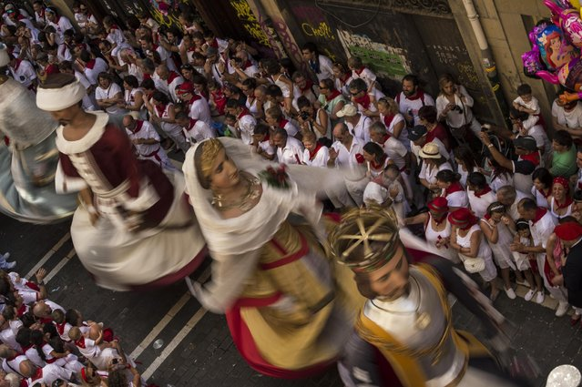 The San Fermin Comparsa Giant Parade passes down the street, at the San Fermin Festival, in Pamplona, Spain, Tuesday, July 7, 2015. (Photo by Alvaro Barrientos/AP Photo)